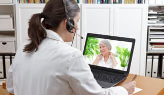 caregiver using laptop via video call to communicate to the senior patient