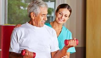 caregiver assisting senior man doing an exercise