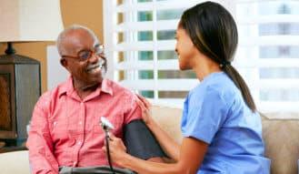 nurse monitoring the health condition of smiling senior man