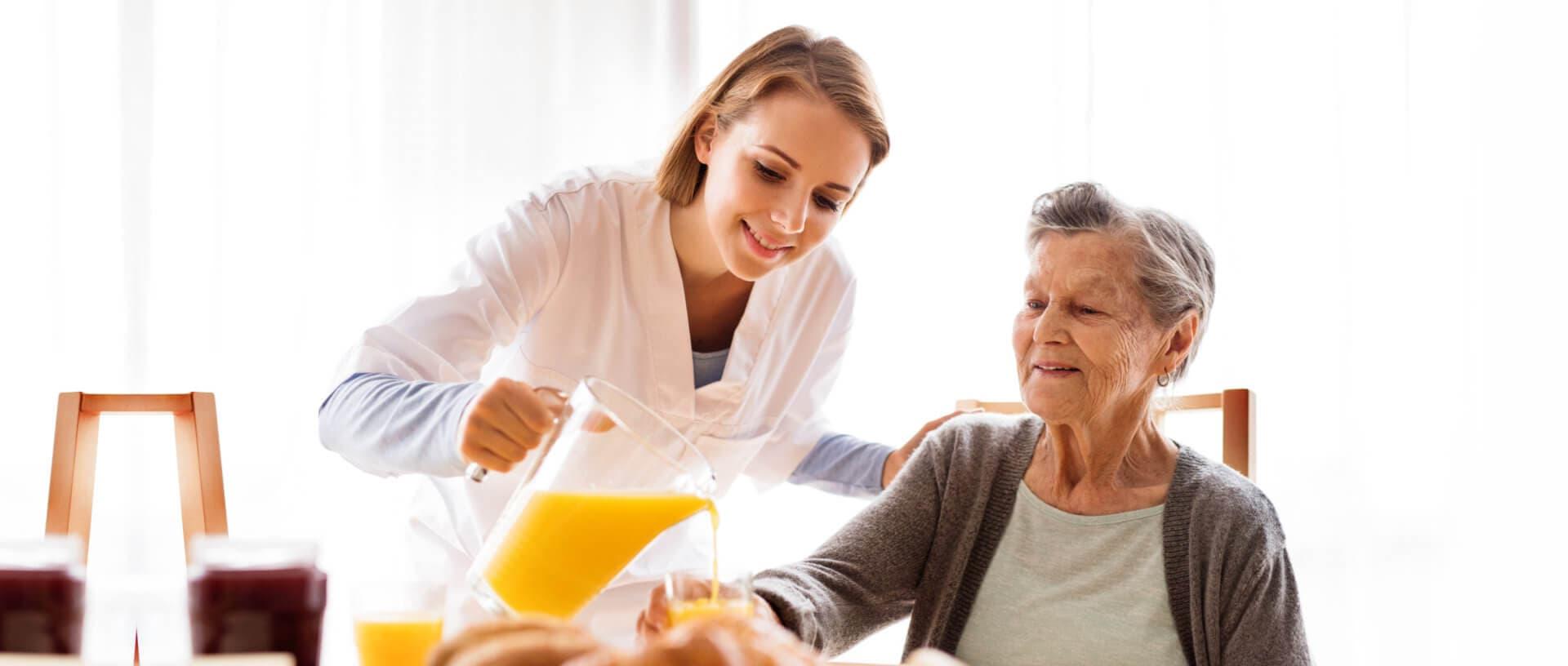 caregiver serving a juice to senior woman