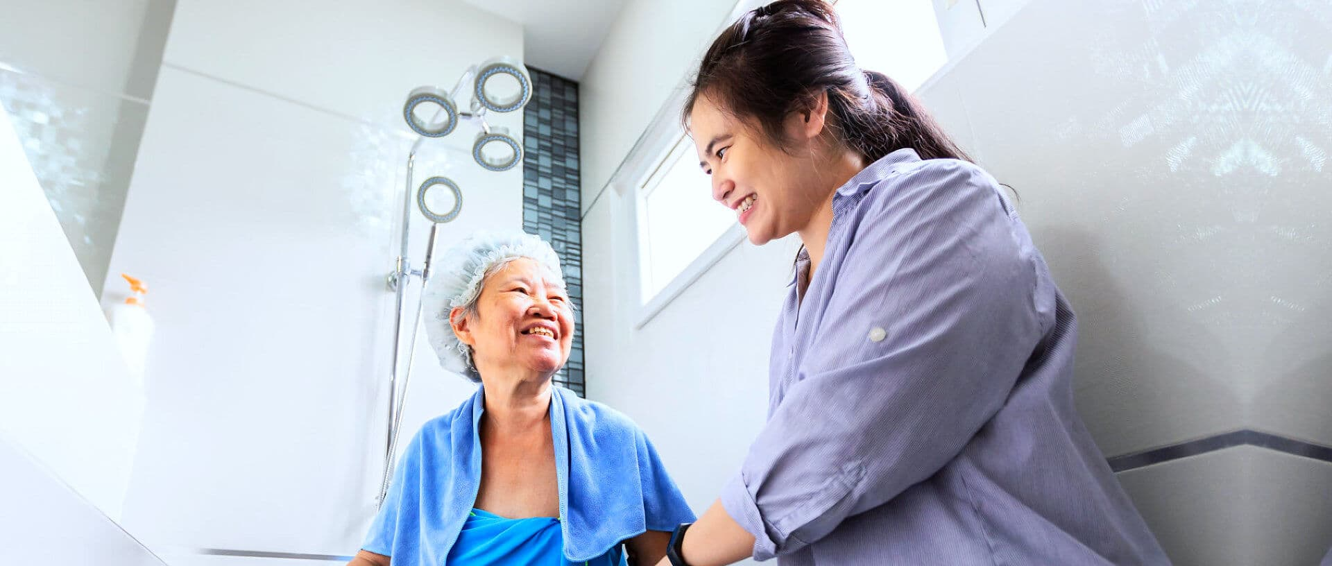 caregiver assisting to senior woman and gave a clean towel