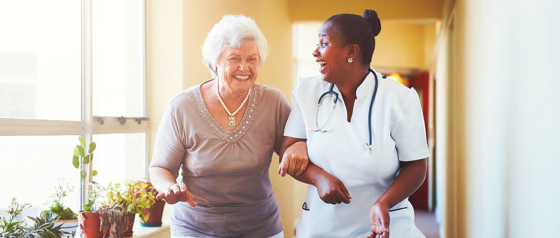nurse and senior woman having a conversation while walking at the hallway