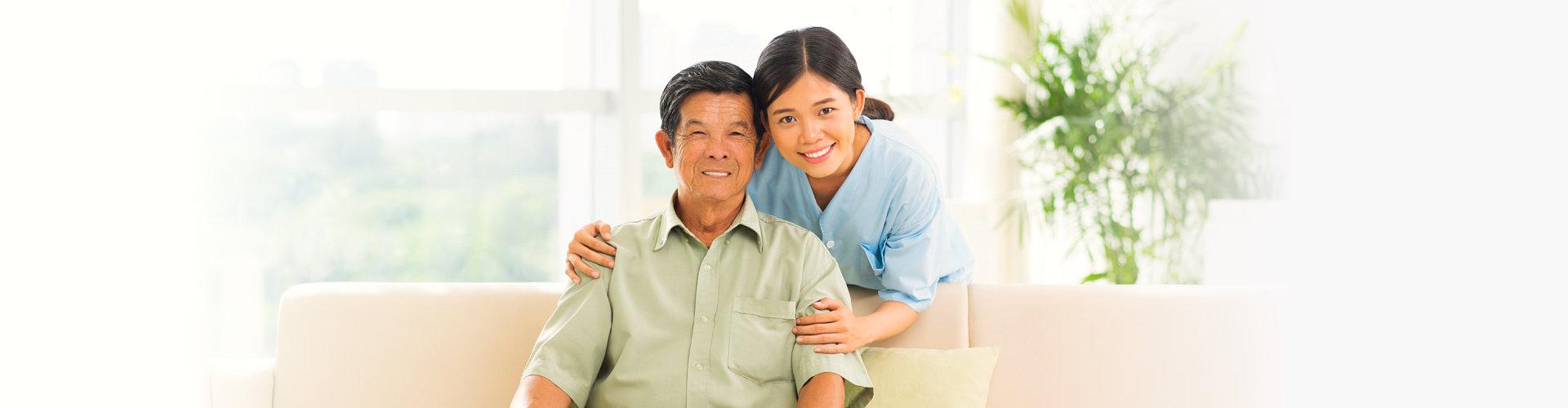 caregiver and senior man are smiling