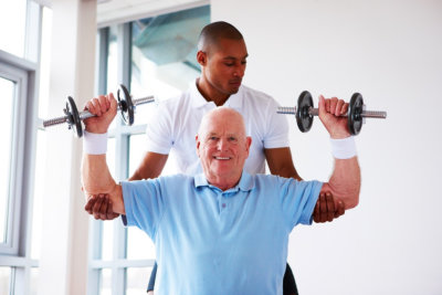 caregiver assisting senior man doing an exercise