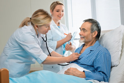 two medical staff monitoring the health condition of senior man