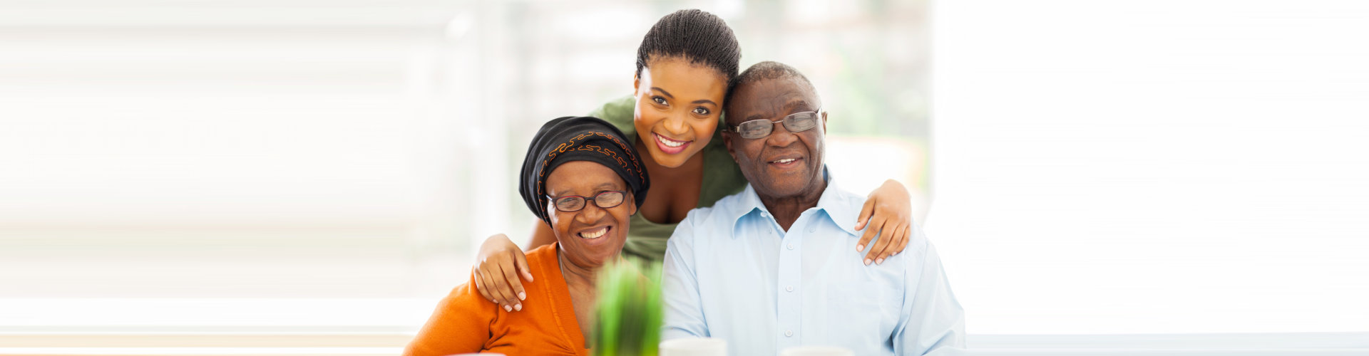 caregiver and senior couple are smiling